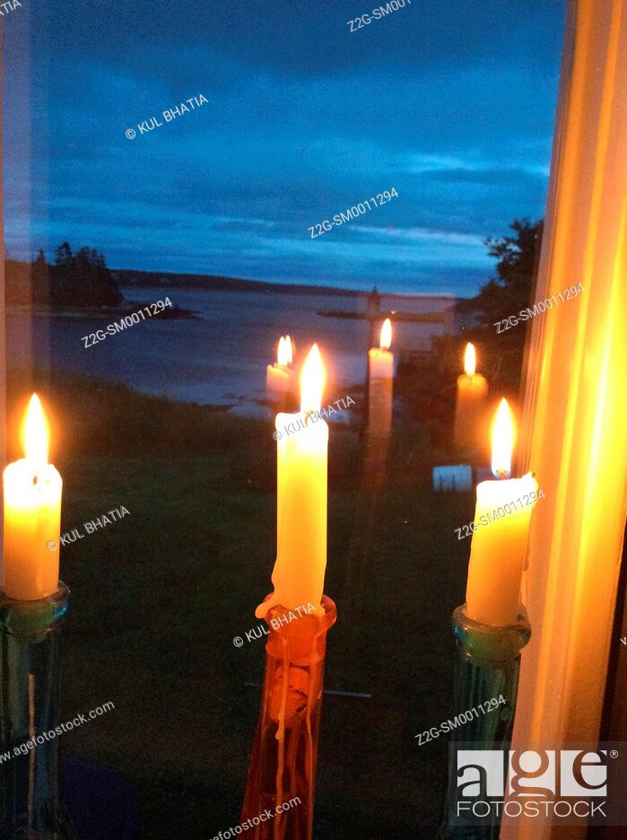 Imagen: Three candles reflected in a window overlooking the ocean at dusk, Halifax, Canada.