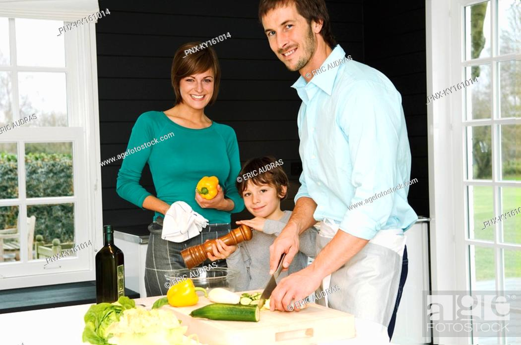 Stock Photo: Mid adult man and a young woman preparing food with their son.