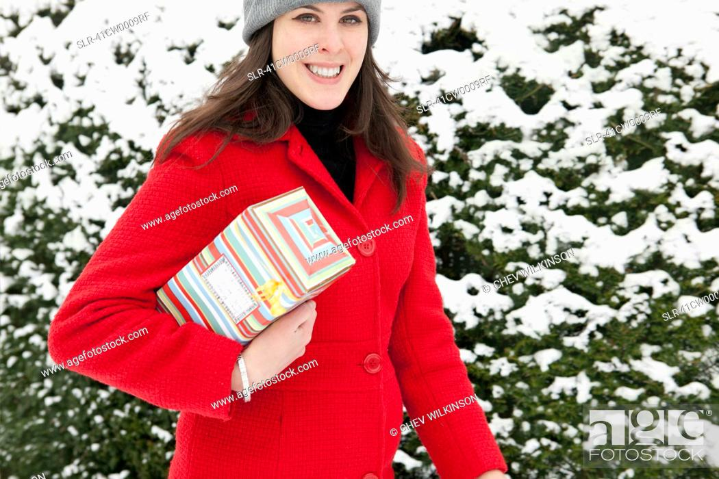 Stock Photo: Woman carrying wrapped gift in snow.
