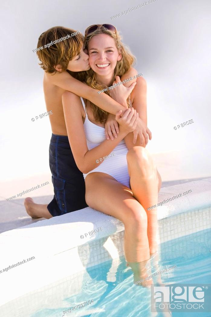 Stock Photo: Boy hugging his mother at the poolside and smiling.