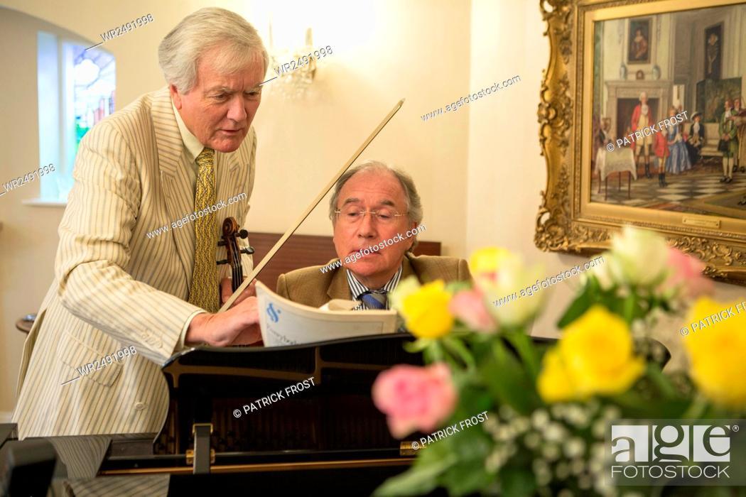 Imagen: Two senior men playing music together.