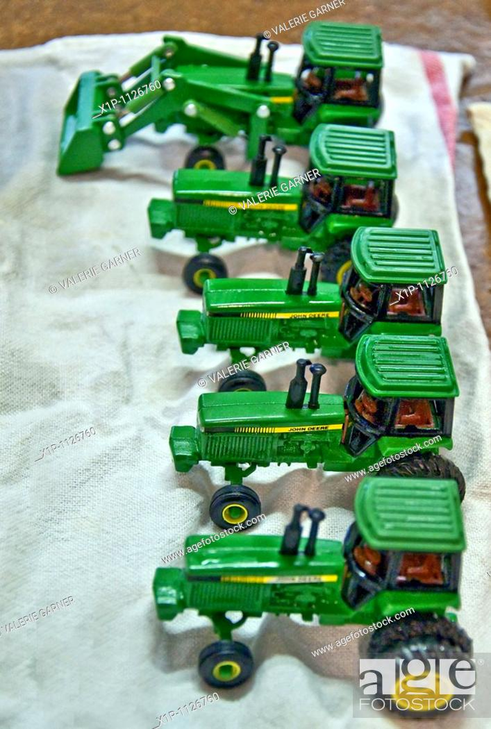 Stock Photo: This vertical image shows a row of 5 green John Deere vintage toy tractors being prepped for an antique show, freshly washed and drying on a towel Focus is.