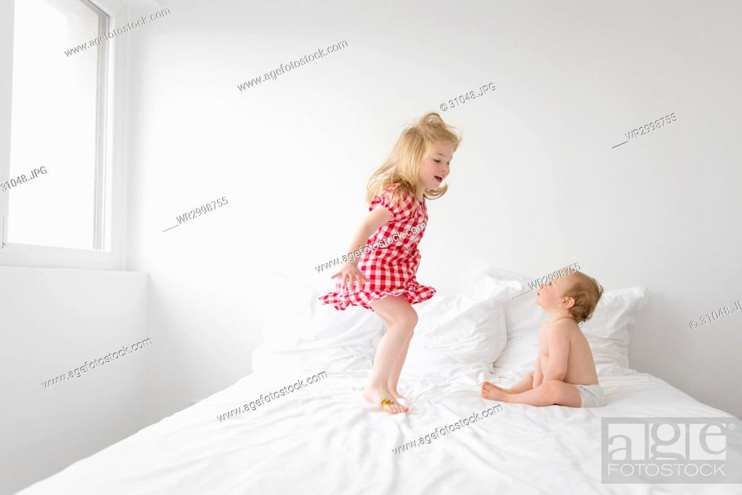 1810a8aeb4e Stock Photo - Smiling blond girl wearing red and white checkered dress  jumping on bed