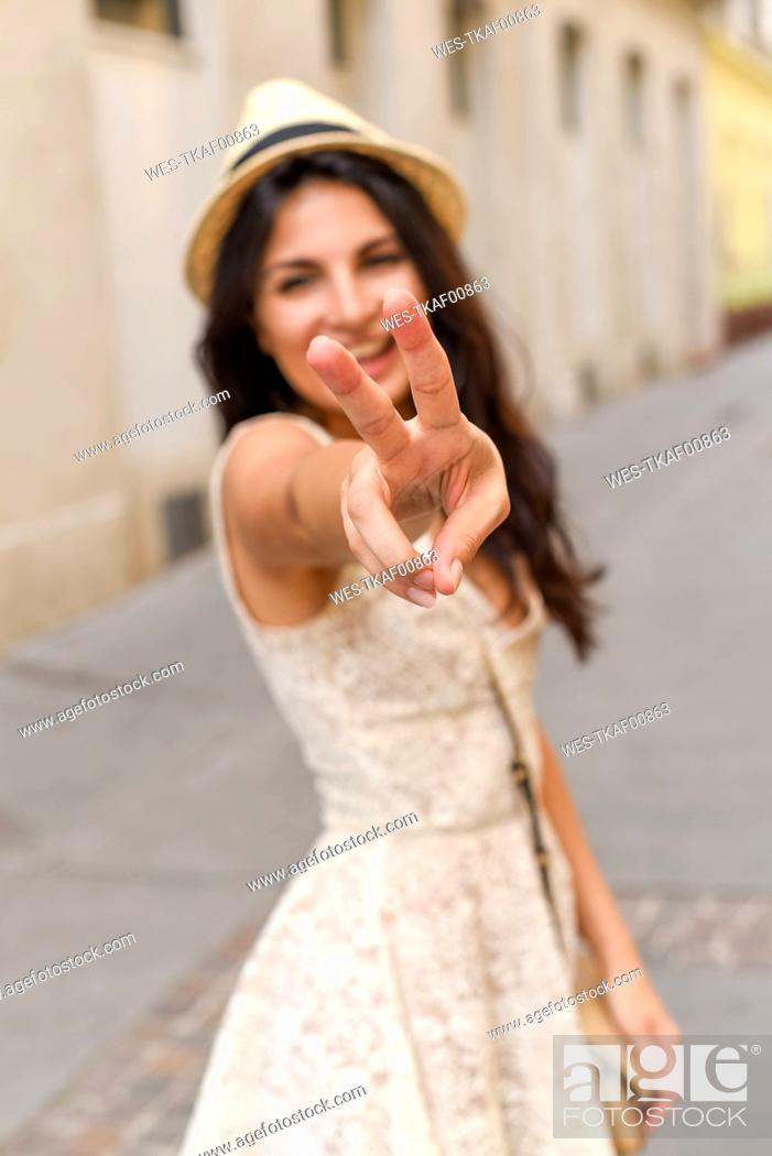 Stock Photo: Happy young woman doing victory sign.