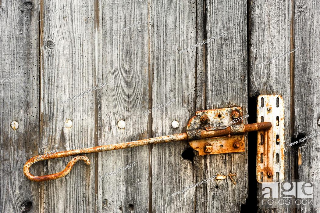 Stock Photo: Old wooden barn door with rusty latch, Charente, France.