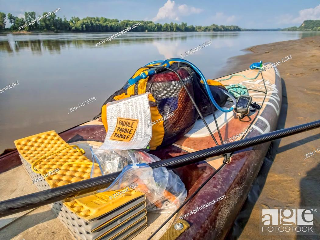 Stock Photo: Dundee, MO, USA - August 10, 2017 - Stand up paddleboard (Starboard Expedition SUP) at rest stop during Missouri RIver 340 race.