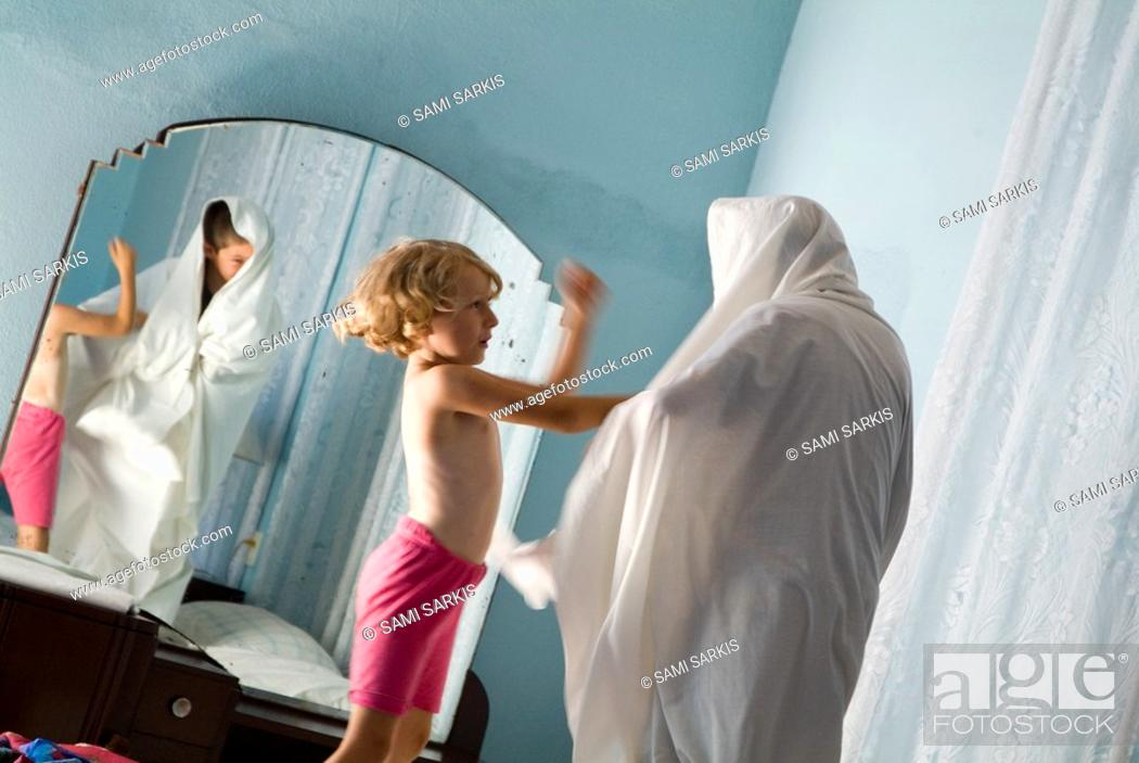 Stock Photo: Brother and sister playing on a bed at the guesthouse in Sancti Spiritus, Cuba.
