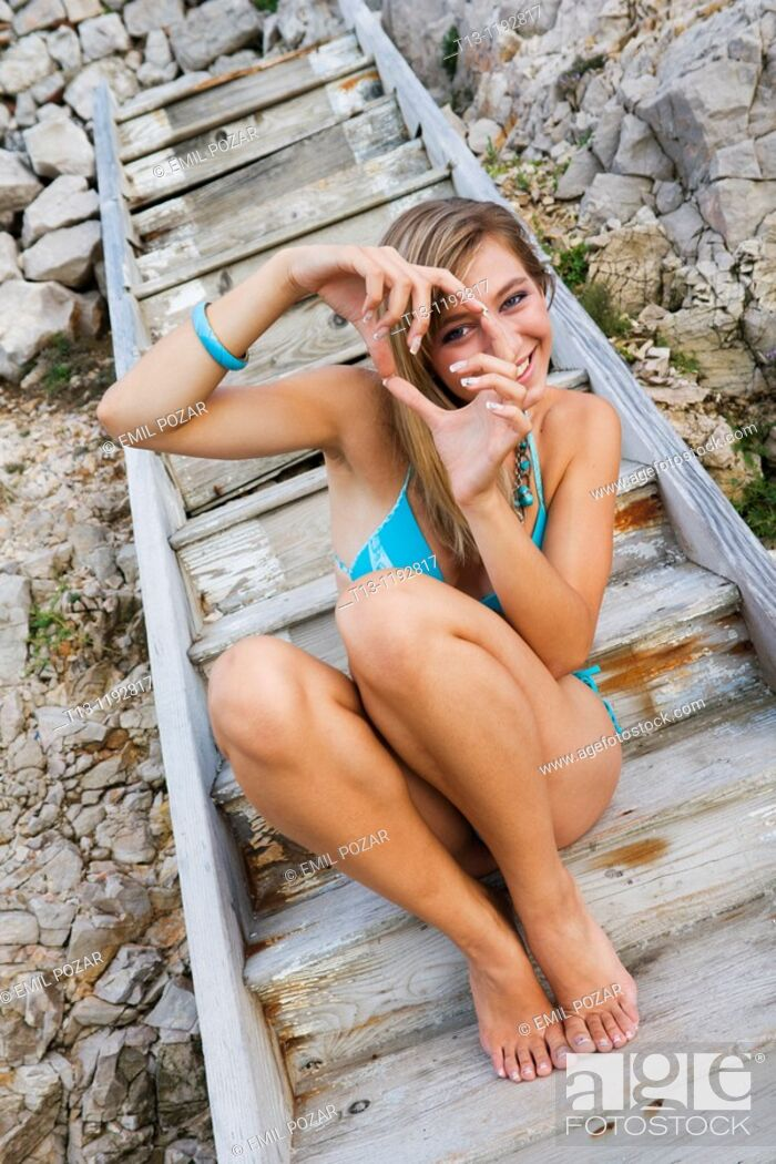 Stock Photo: Young woman in a swimsuit is pretending to take a snap picture with hands.