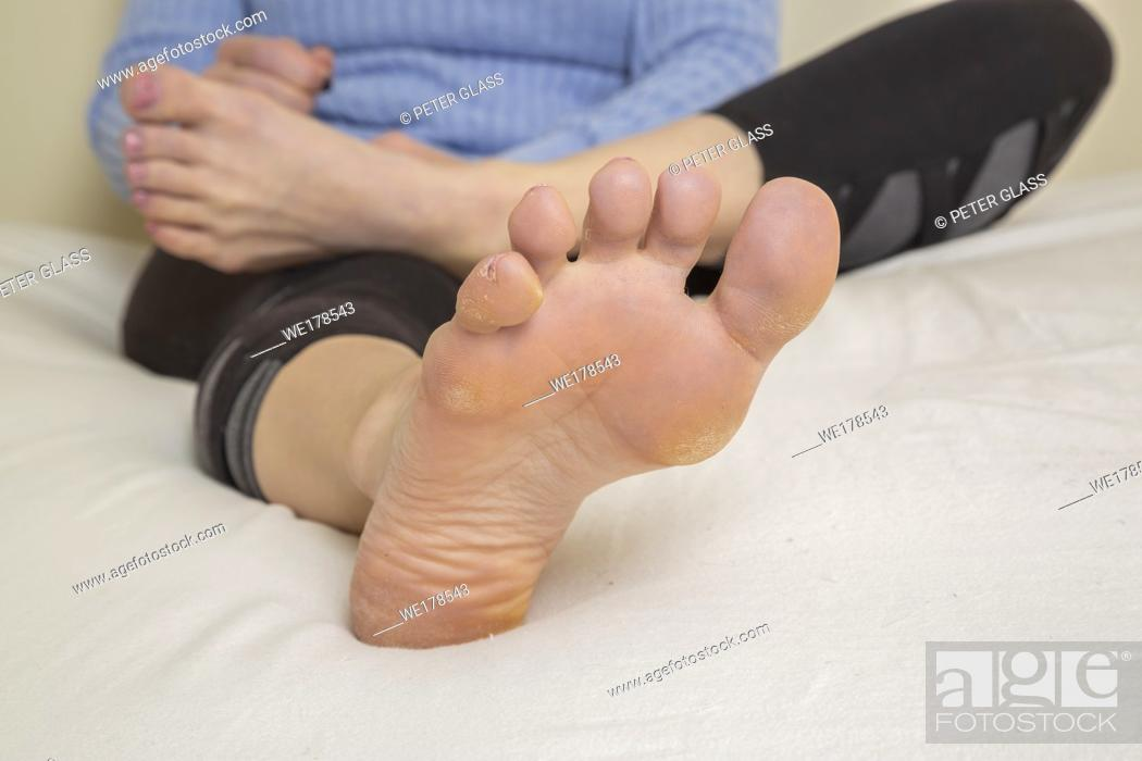 Stock Photo: Close-up of a young woman's feet and legs with her torso behind them, as she sits on her bed.