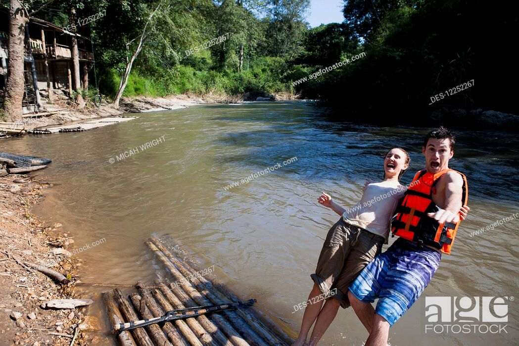 Imagen: Young tourists bamboo rafting down the river; Chiang Mai, Thailand.
