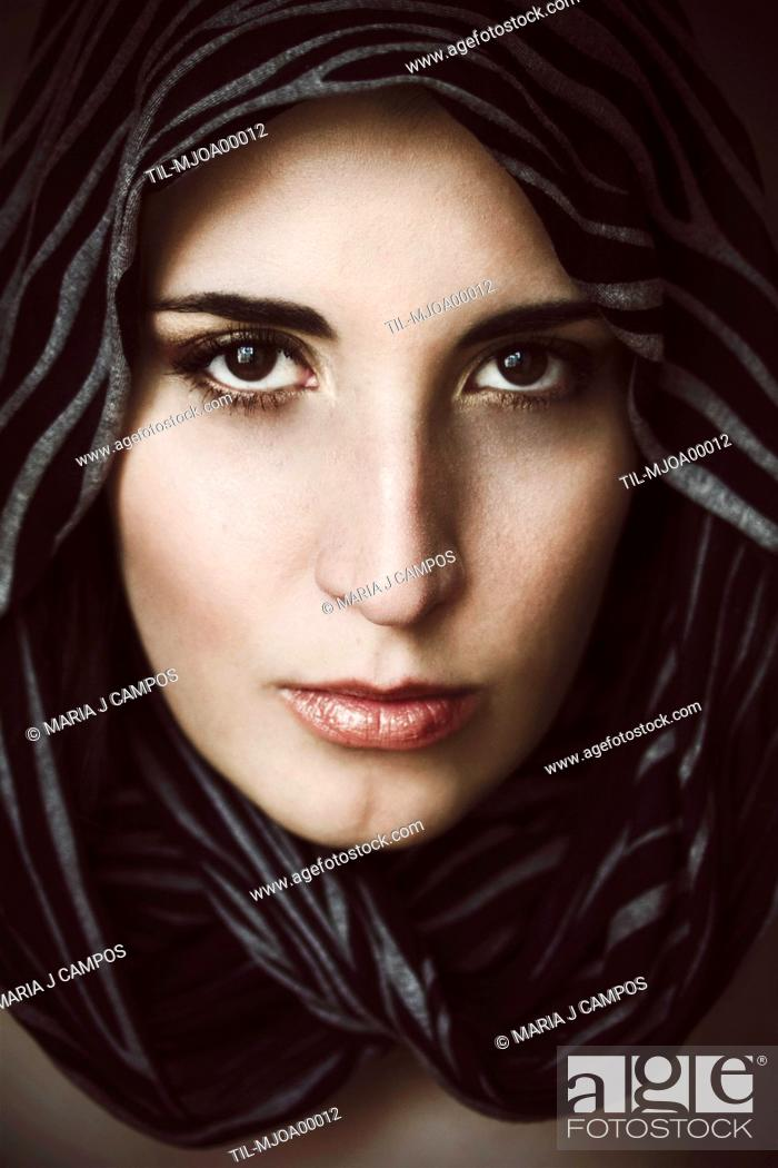 Stock Photo: Close-up portrait of a young woman with pale skin and brown eyes, with a scarf around her face staring at the camera.