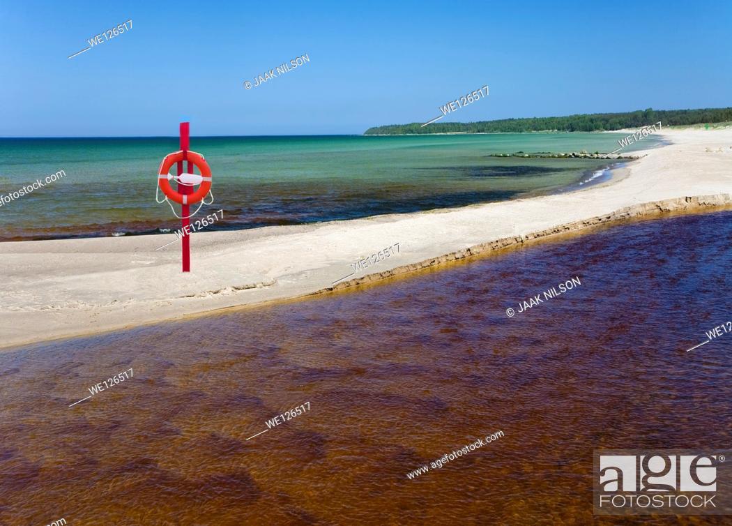 Stock Photo: Life bouy, life belt hanging on post. Sandy beach in Vääna-Jõesuu river mouth in Estonia. Baltic sea.