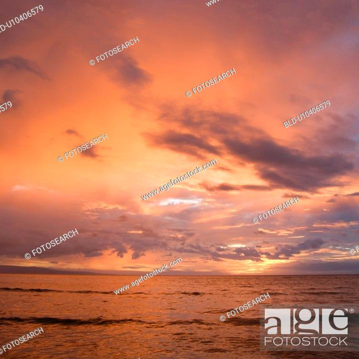 Stock Photo: Orange glowing clouds during sunset on coast.