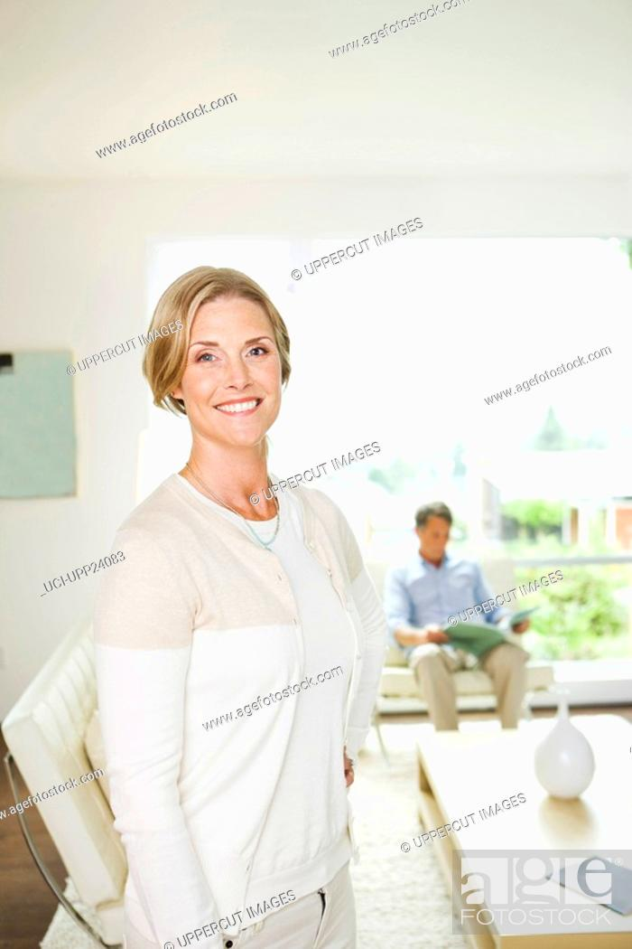 Stock Photo: Portrait of woman standing in living room.