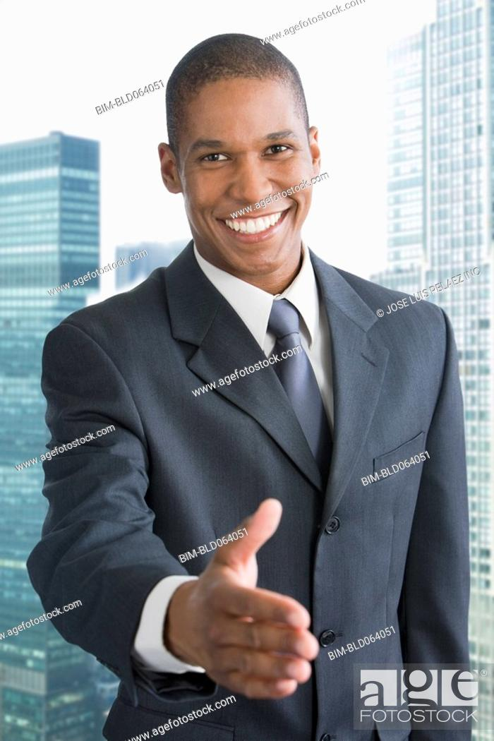 Stock Photo: Mixed race businessman offering hand to shake.