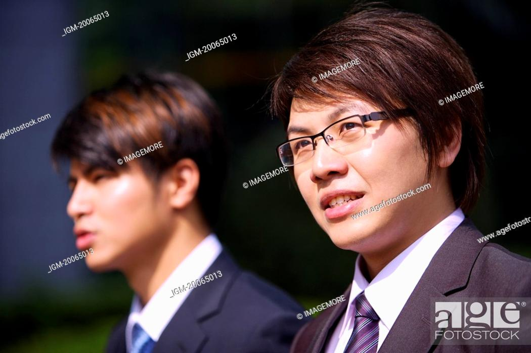 Stock Photo: Two businessmen looking away together.