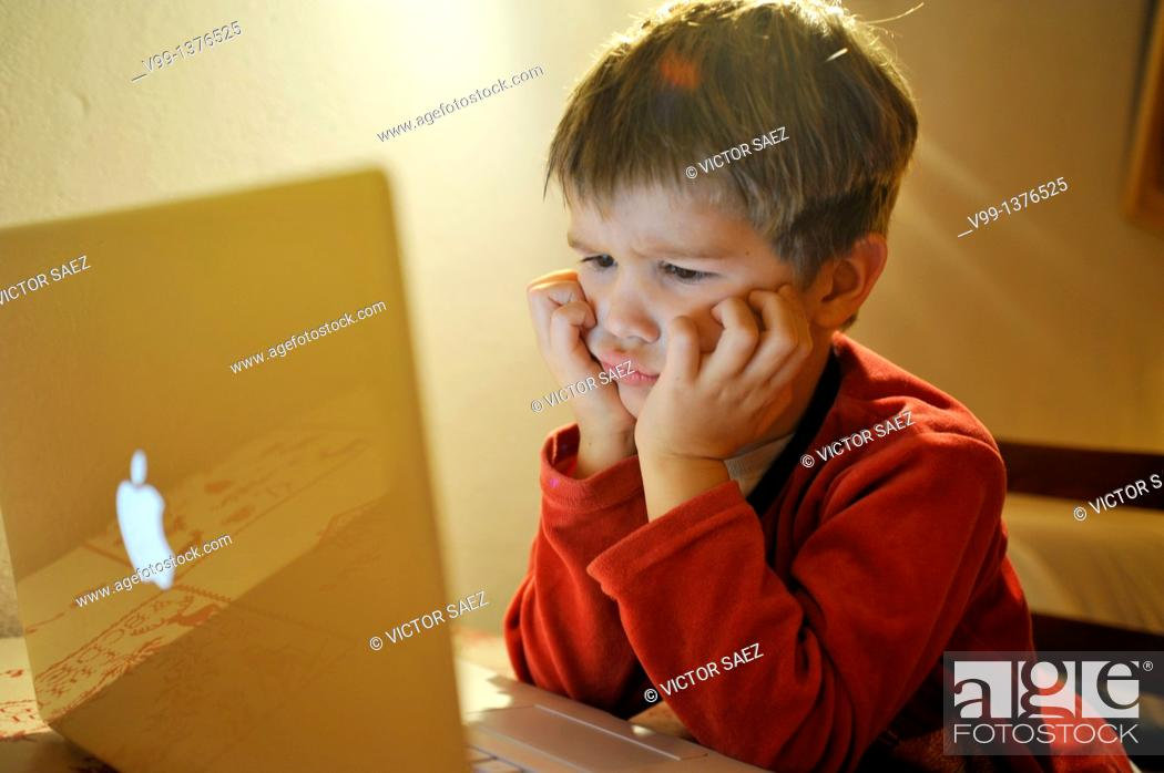 Stock Photo: young boy who watches a movie on computer.