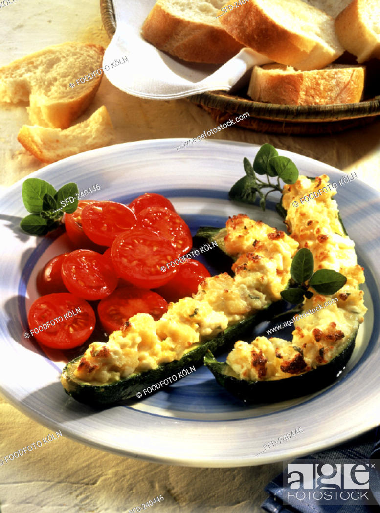 Stock Photo: Courgettes with sheep's cheese and tomato salad, baguette.