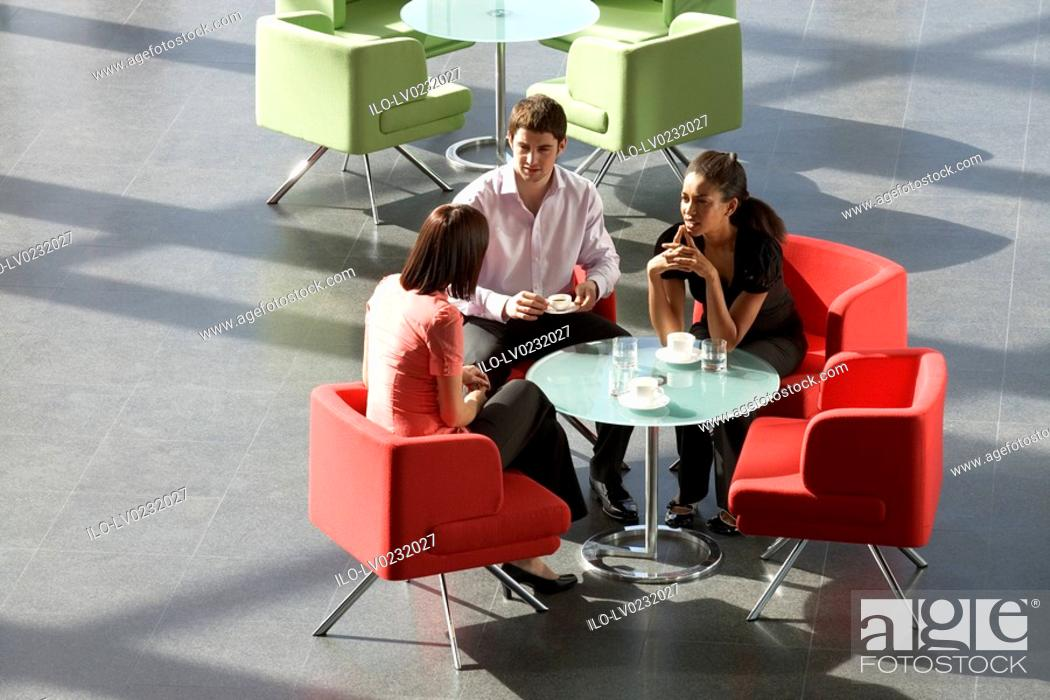 Stock Photo: Three business colleagues having a meeting over a hot drink in an office building.