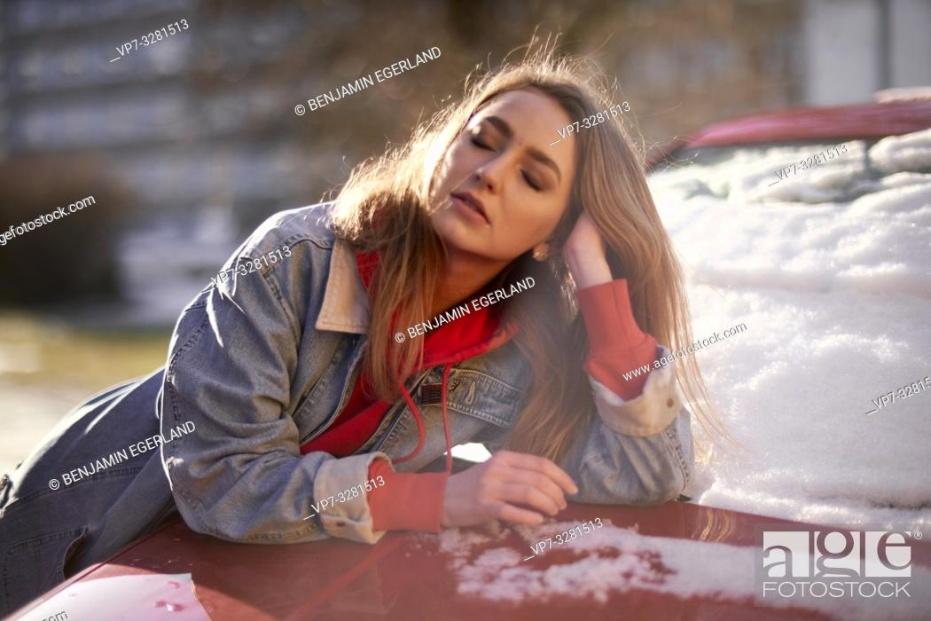 Stock Photo: young woman leaning on car outdoors, winter seasons, in Cottbus, Brandenburg, Germany.