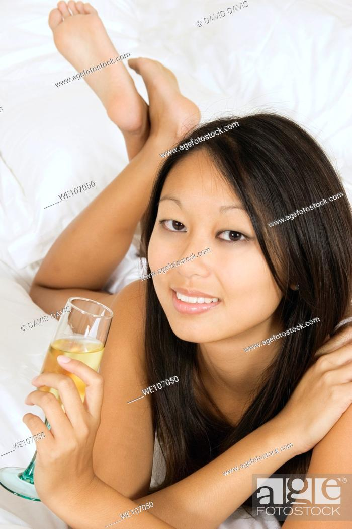 Stock Photo: Asian woman in early 20's laying in bed with a glass of white wine.