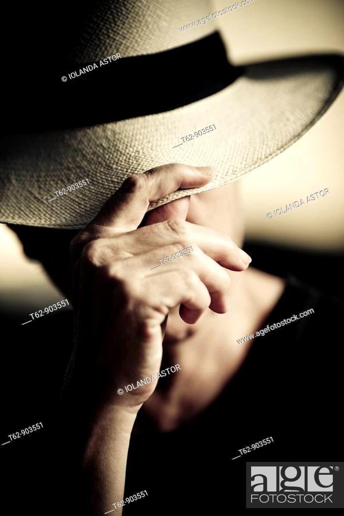 Stock Photo: A woman is protected from the sun with his Panama hat.
