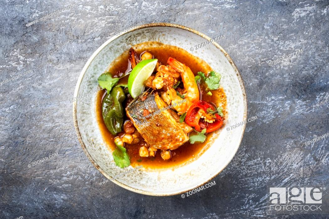 Stock Photo: Modern style traditional Mexican seafood pozole soup with fish, king prawns and hominy in a clear sauce served as top view in design bowl.