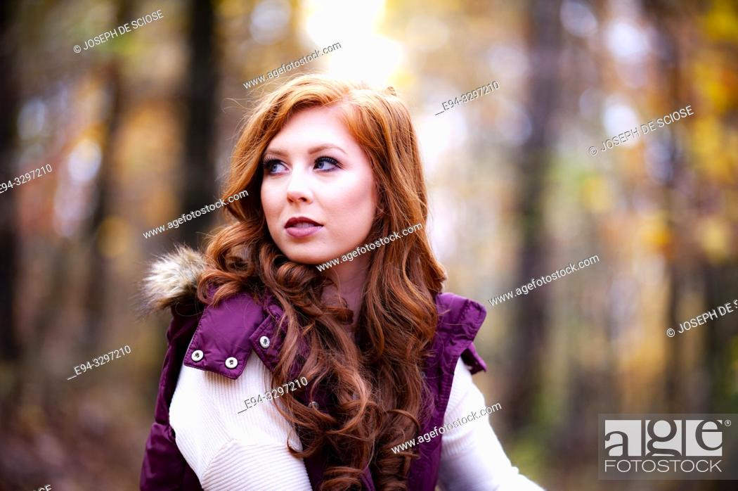 Stock Photo: Portrait of a 25 year old redheaded woman in a forest setting.
