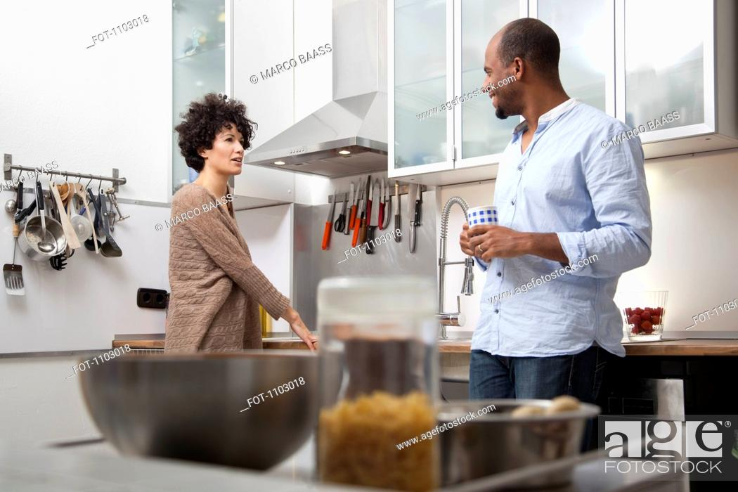 Stock Photo: A couple standing in an apartment kitchen.