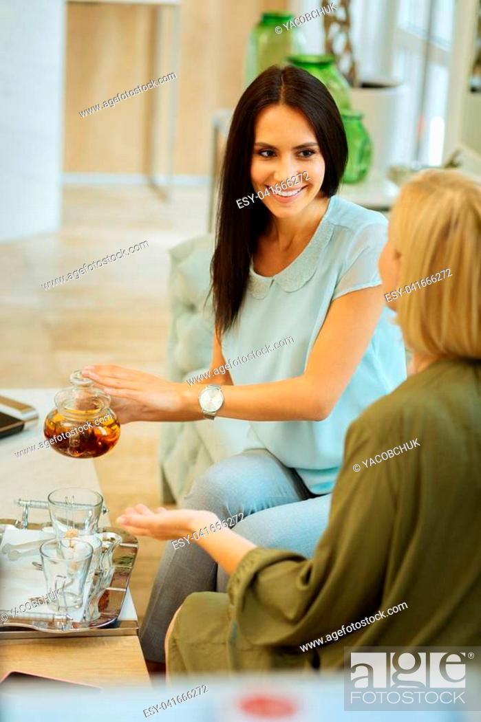 Stock Photo: Pleasant interaction. Attractive joyful woman looking at her motherwhile pouring tea.