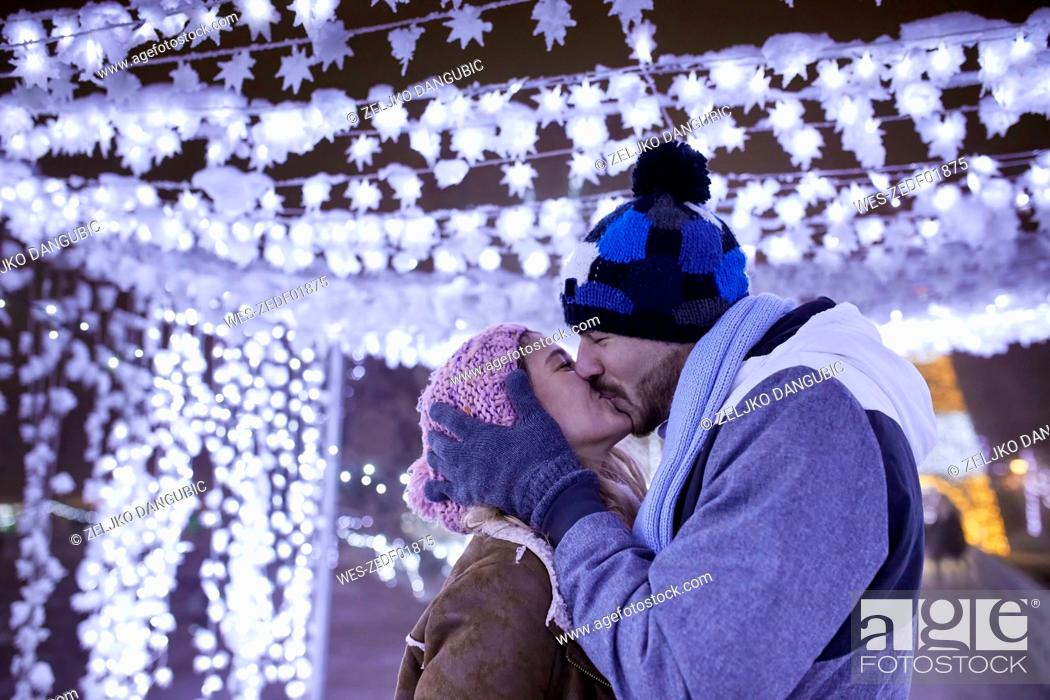 Stock Photo: Happy young couple kissing in winter decoration.