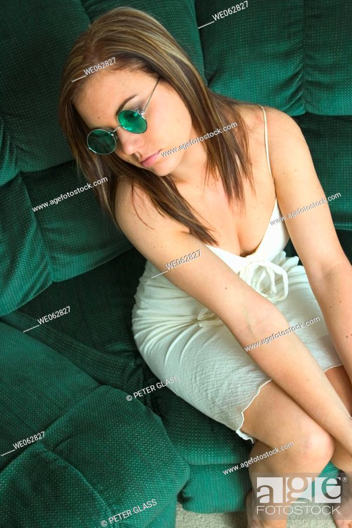 Stock Photo: Young woman sitting on her sofa, wearing sunglasses.
