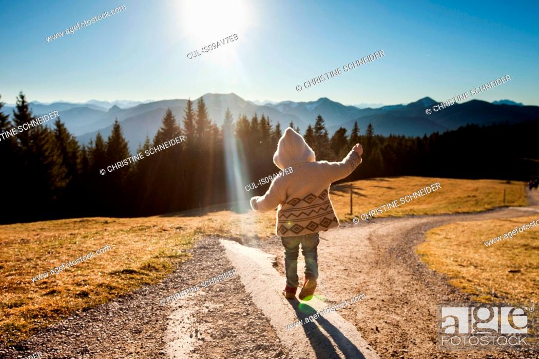 Stock Photo: Rear view of female toddler toddling on sunlit dirt track, Tegernsee, Bavaria, Germany.
