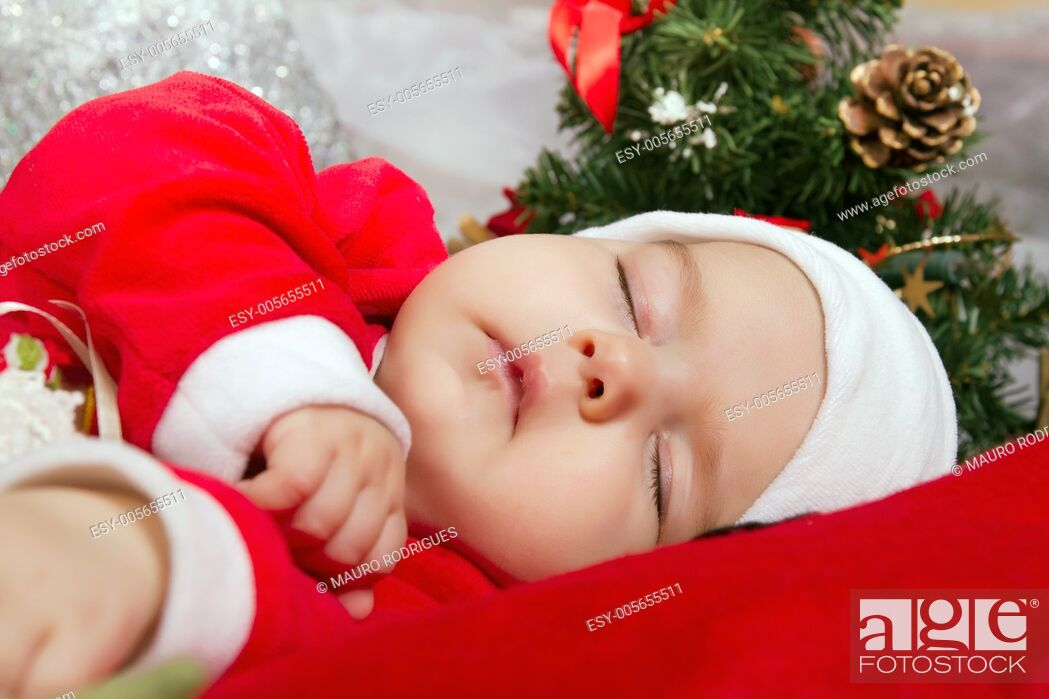 Stock Photo: View of a newborn baby on a Christmas suit sleeping.