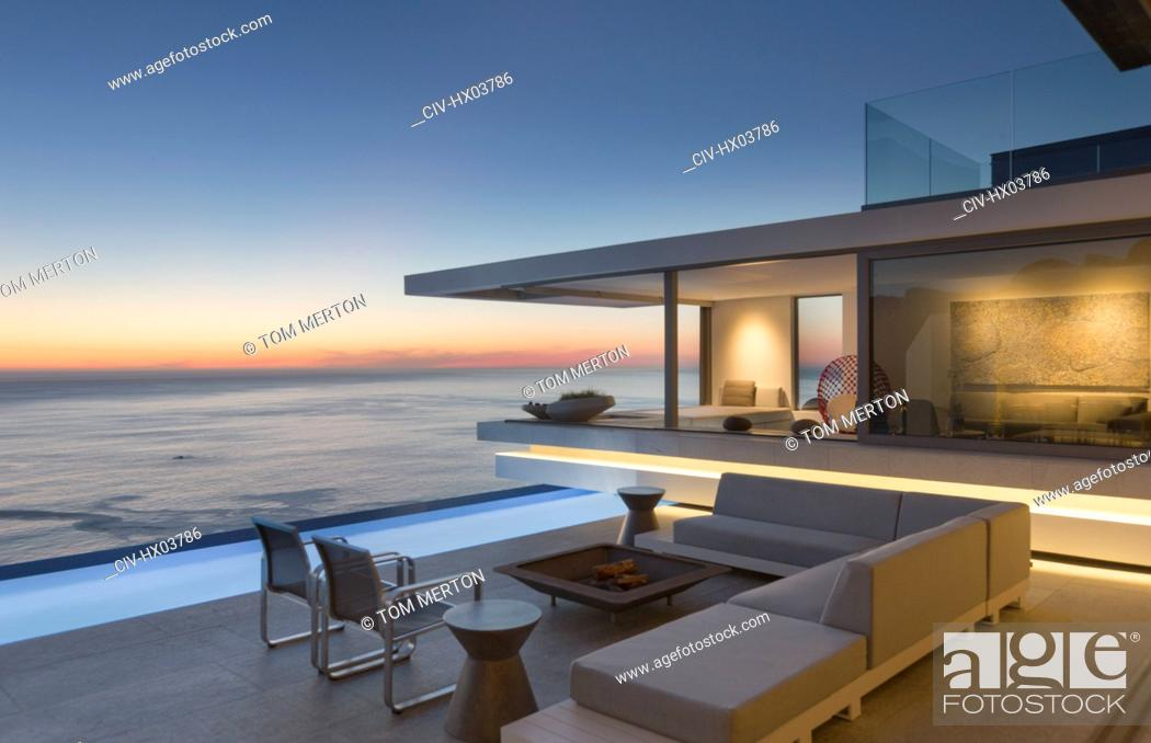 Stock Photo: Illuminated modern, luxury home showcase exterior patio with sofa and lap pool with ocean view at dusk.