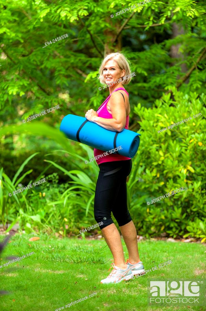 Stock Photo: A 56 year old blond woman dressed in fitness clothing and holding a yoga mat, smiling at the camera, outdoors.
