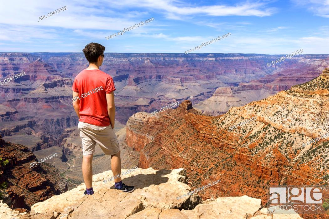 Stock Photo: Young man surveying the Grand Canyon from one of the many overlook points on the South Rim. Behind him are the red-rocks of the North Rim.