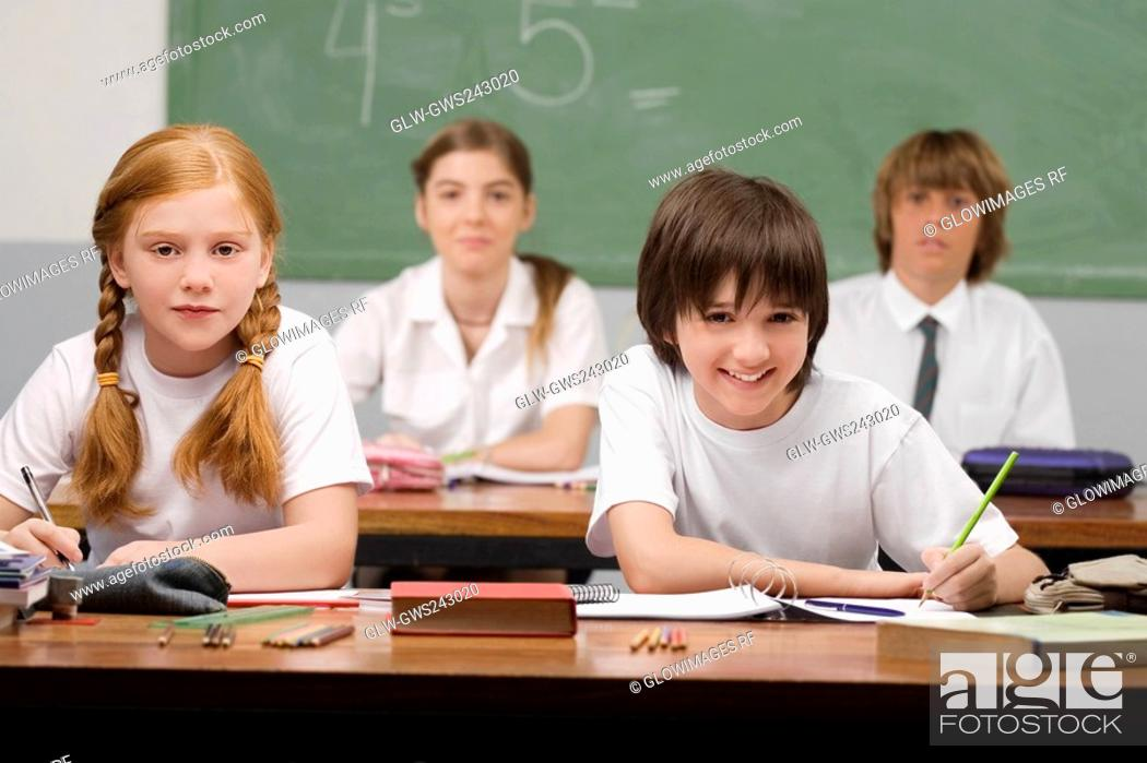 Stock Photo: Portrait of four school students sitting in a classroom.