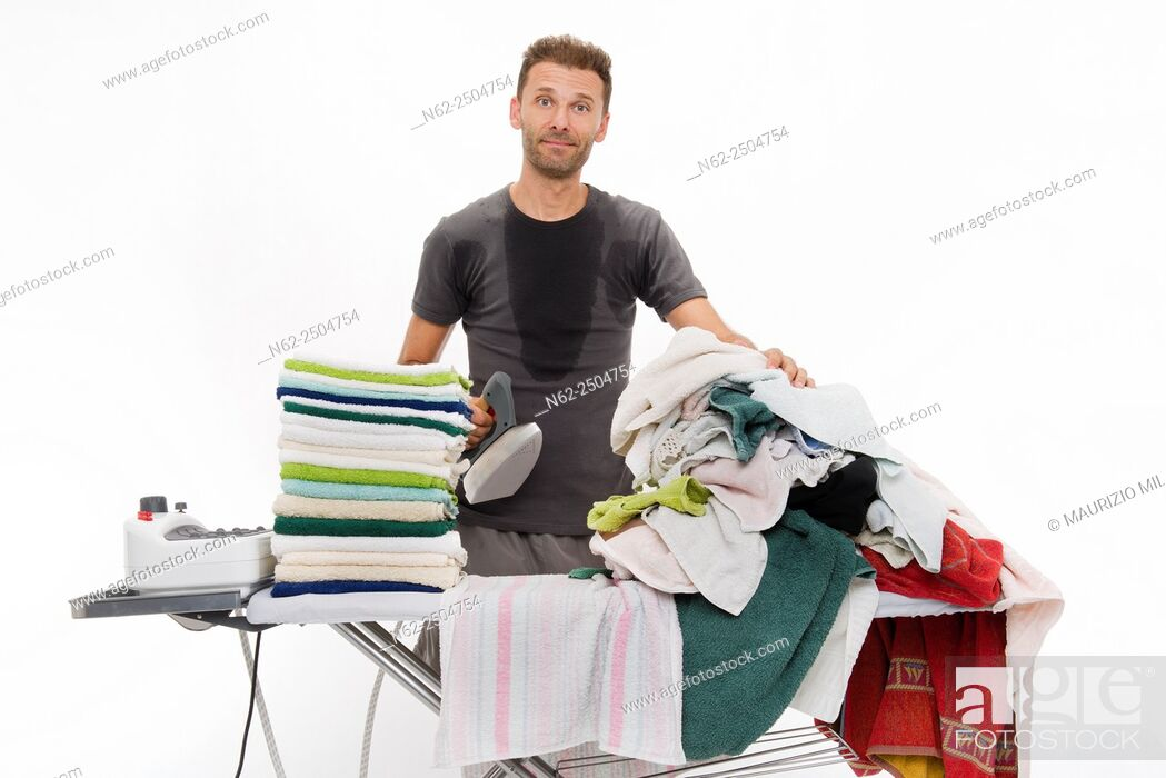 Stock Photo: Very sweaty man behind a ironing board full of clothing looks smugly.