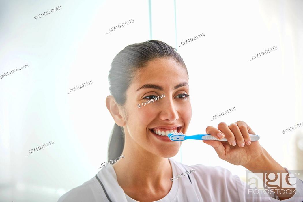 Stock Photo: Woman brushing teeth with toothbrush.