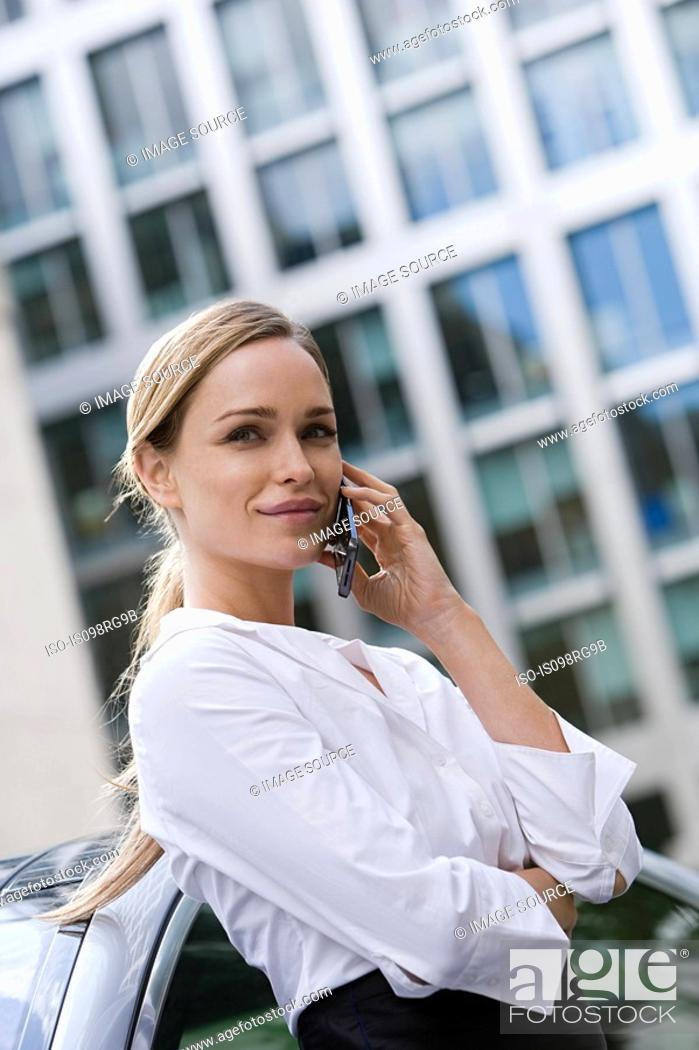 Stock Photo: Young businesswoman using a cellular telephone.