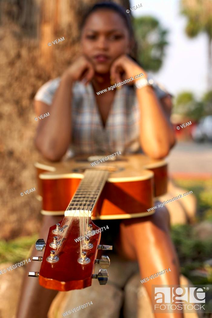 Photo de stock: Woman with guitar sitting outdoors.
