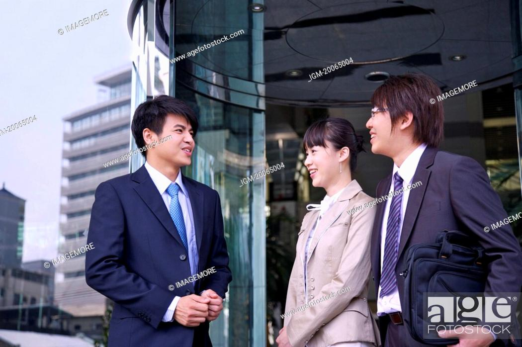 Stock Photo: Three colleagues standing and talking together with smile.