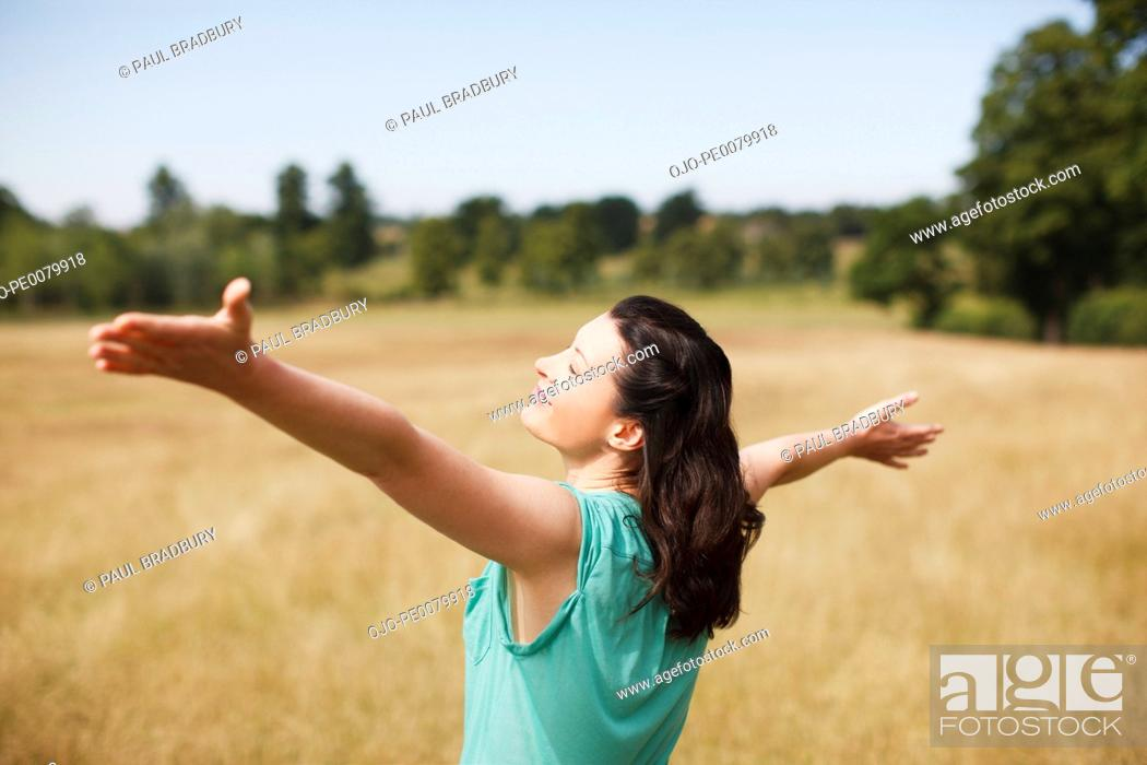 Stock Photo: Woman with arms outstretched in sunny rural field.