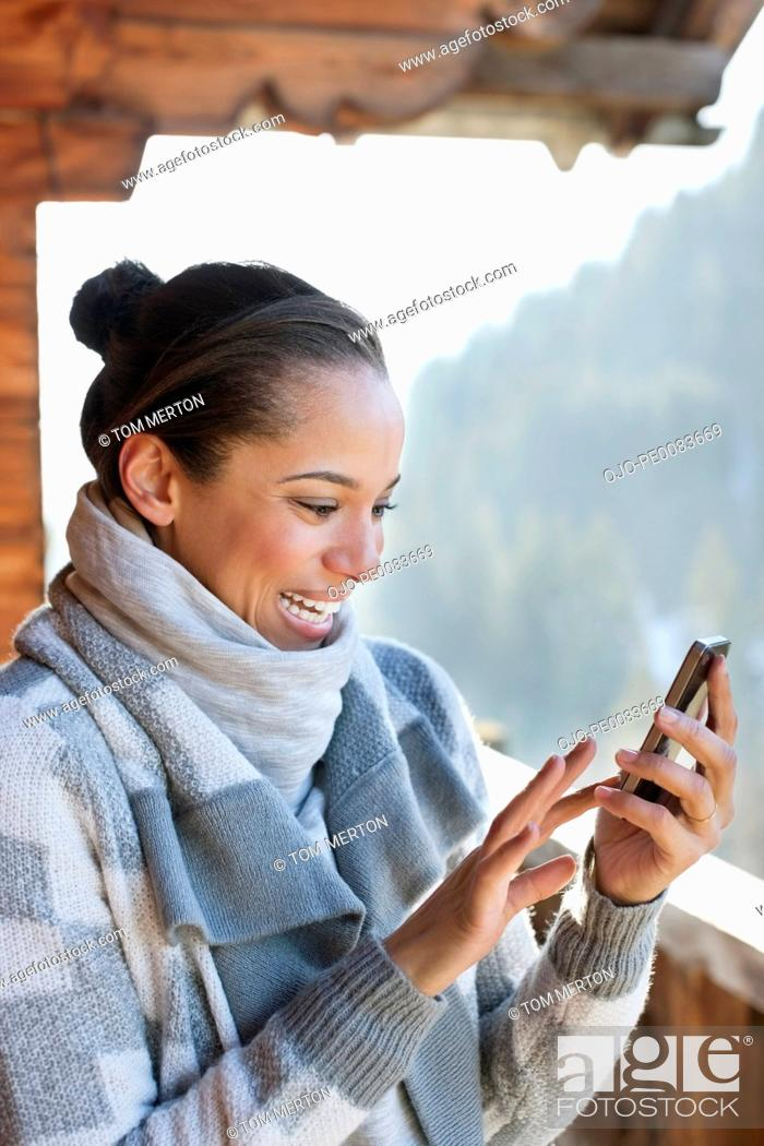 Stock Photo: Smiling woman checking cell phone on cabin porch.
