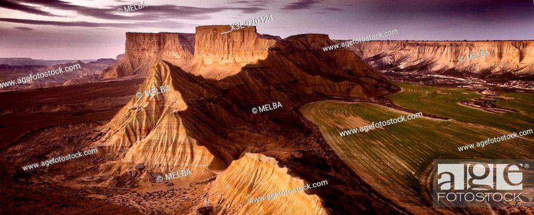 Stock Photo: Dusk in Bardenas Blancas area, grain fields on the right, Bardenas reales natural park, Navarre, Spain.