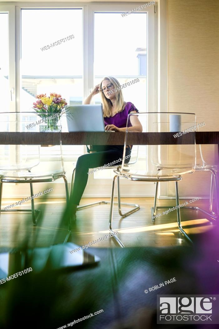Stock Photo: Businesswoman sitting at meeting table looking at laptop.