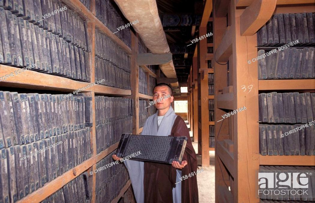 Stock Photo: Buddhist monk presentinf one of the 80000 wooden blocks on which are carved the complete Buddhist scriptures of 'Tripitaka', Haein-sa monastery.