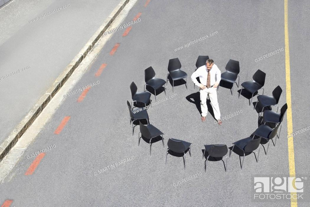 Stock Photo: Businessman standing in circle of office chairs in roadway.