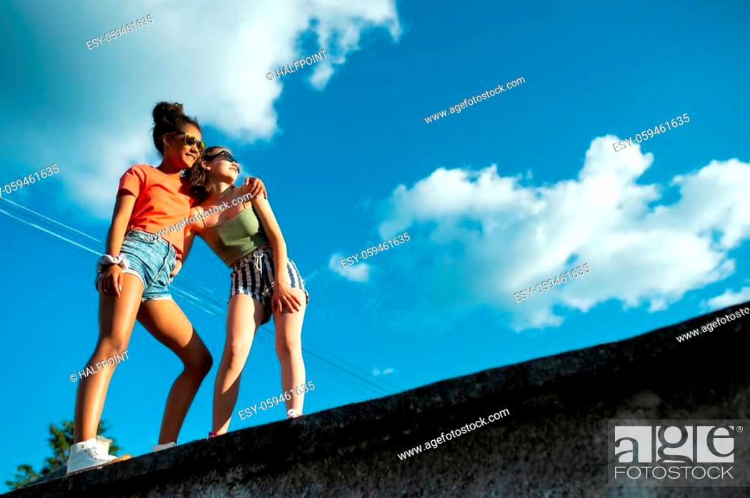 Imagen: Cheerful young teenager girls friends with skateboards outdoors in city, standing. Copy space.